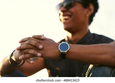 Man wearing round smartwatch. Black young man Closeup of hands and wrist with smart watch screen.
