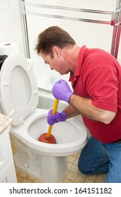 Man wearing rubber gloves and using a plunger to unclog the toilet.