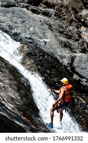 Man wearing safety gear life jacket helmet, rappelling rocky waterfall hanging of a rope at the bottom of a waterfall