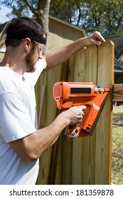 Man wearing safety glasses uses a portable nail gun to attach wood pickets to the rail as he builds a privacy fence in the backyard.