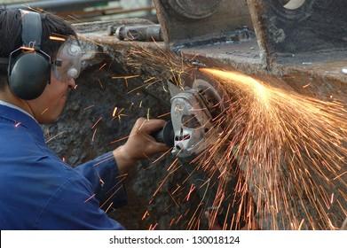 man wearing safety goggles grinds welding splatter off a machine