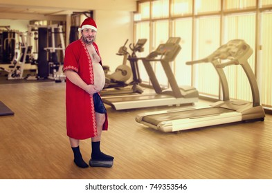 Man wearing Santa suit posing in fitness room. Big belly man has already gained weight during Christmas days. Blurred indoor background