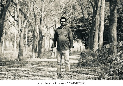 Man wearing shirt and jeans standing around a place