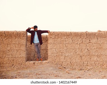Man wearing shirt standing around an incomplete clay made house