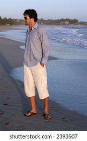 man wearing shirt and white pants on the beach during vacation