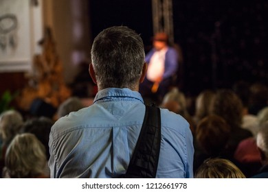 Man wearing a single strap backpack is listening to a public conference given in a church - Pictured from the back with blurry people in the background