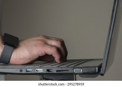 A man wearing a smartwatch while holding a laptop.
