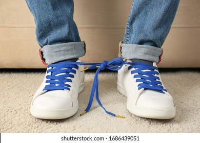 Man wearing sneakers with tied together laces, closeup. April fool's day