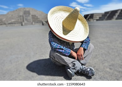 Man wearing Sombrero hat having a siesta, an afternoon rest or nap, especially one taken during the hottest hours of the day in a hot climate, at the Pyramids of Teotihuacan, Mexico.
