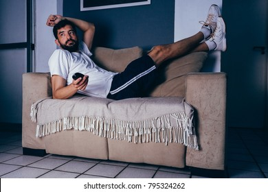 Man wearing sportswear lying on the couch watching TV. Laziness concept