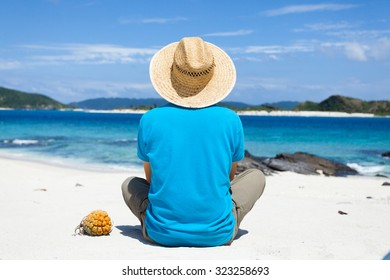 Man wearing a straw hat, sitting on a deserted tropical island beach, Zamami Island of the Kerama Islands National Park, Okinawa, Japan