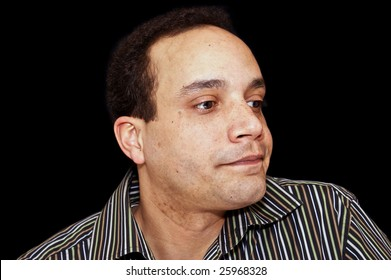 man wearing striped shirt against black background with strange expression on face