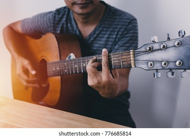 Man wearing a striped shirt playing guitar in his room with romantic atmosphere full of symphonic music.