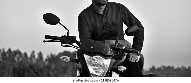 Man wearing stylish jeans wear sitting on a bike isolated black and white photo