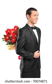 Man wearing suit and bow tie hiding a bouquet of flowers behind his back isolated on white background