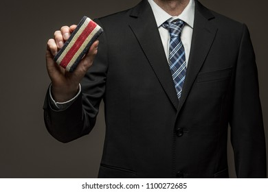 Man wearing suit holding eraser