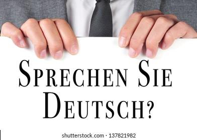 a man wearing a suit holding a signboard with the sentence sprechen sie deutsch? do you speak german? written in german on it