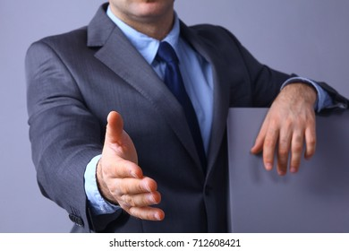 Man wearing a suit offering to shake hands standing near board