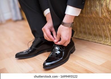 Mann mit einem Anzug, der seine braunen Schuhe anzieht. Hände und Schuh, Nahaufnahme. Nahaufnahme von männlichen Händen Schnüren schöne elegante Schuhe.Hochzeitstag. Bräutigam schnürt seinen Schuh