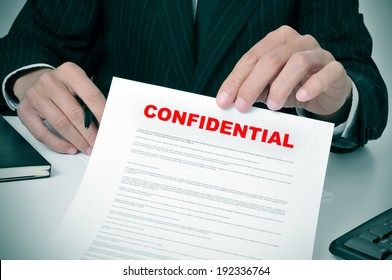 a man wearing a suit showing a document with the text confidential written in it