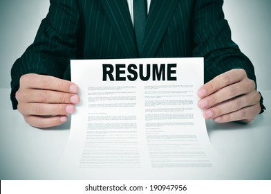 a man wearing a suit showing his resume