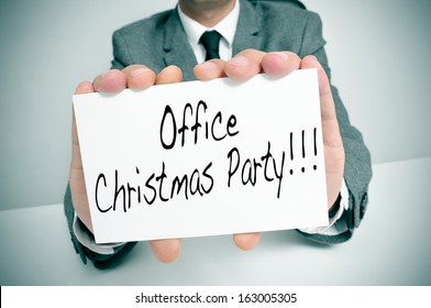 a man wearing a suit sitting in a desk holding a signboard with the text office christmas party written in it