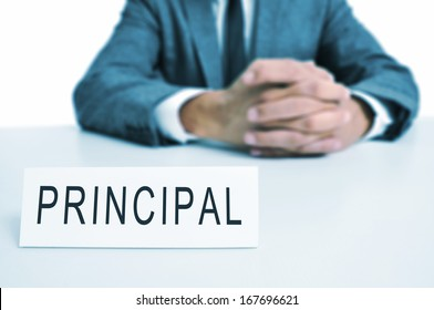 a man wearing a suit sitting in a desk with a signboard in front of him with the word principal written in it