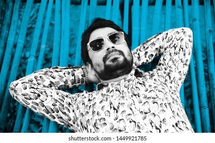 Man wearing sunglass lying on a blue bamboo surface