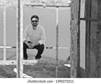 Man wearing sunglass sitting on a metallic object