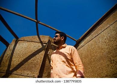 Man wearing a sunglass standing inside a metallic structure