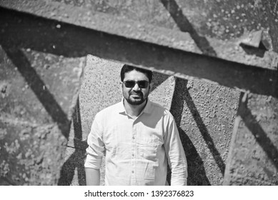 Man wearing sunglass standing in a place black and white photo