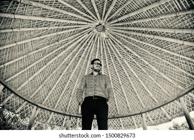 Man wearing sunglass standing under a bamboo made ceiling design