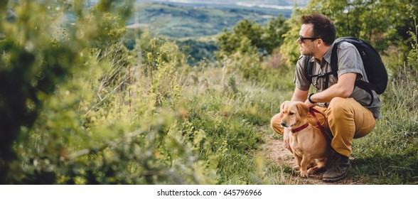 Man wearing sunglasses with a small yellow dog resting at the hiking trail