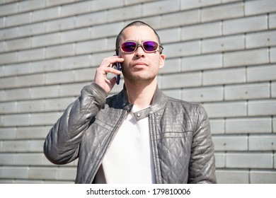 Man wearing sunglasses talking on his cell phone