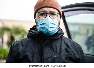 a man wearing a surgical face mask while outside in the rain. government orders people to wear any face mask during the global pandemic of COVID-19 to prevent further outbreaks