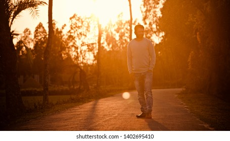 Man wearing t shirt and jeans standing in a road in the afternoon
