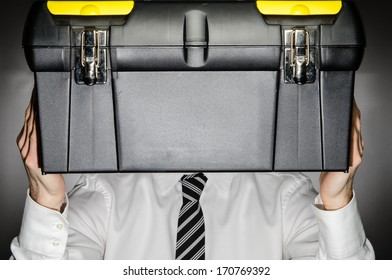Man wearing tie holding toolbox in front of his face