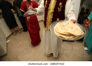 """Man wearing tradtional Moroccan garb serves Jewish ethnic food called 'mufleta' on a platte.r This food is traditionally made at the end of the Passover holiday at a Jewish event called """"Mimuna"""""""