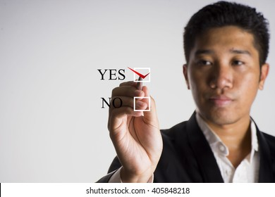 A man wearing tuxedo writing checklist with the options of yes or no on screen, select focus  - business concept
