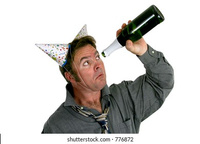 A man wearing two party hats and looking sadly up inside and empty bottle of champagne.