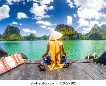 man wearing a Vietnamese hat enjoying the magnifiecent sight of Ha Long bay limestone rocks on a beautiful sunny day during a boat cruise, UNESCO world heritage site, Vietnam
