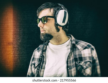 Man Wearing Vintage Headphones. A man listening to large, retro headphones on a black background. Classic, authentic film look.