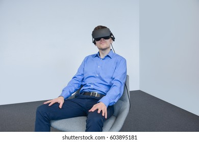 Man wearing virtual reality device. Side close view, smiling face expression, sitting in the chair with  hands raised. Business casual style, over grey background. New Virtual  device 2017.