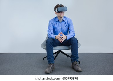 Man wearing virtual reality device. Side view, calm face expression, sitting in the chair. Business casual style, over grey background.