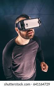 Man wearing virtual reality device, studio shot