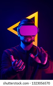 Man wearing virtual reality goggles interacting with VR using hands motion control. VR head set videogame in 80's synth wave and retrowave glowing triangle futuristic aesthetics.