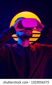 Man wearing virtual reality goggles. VR head set videogame in 80's synthwave and retrowave futuristic aesthetics.