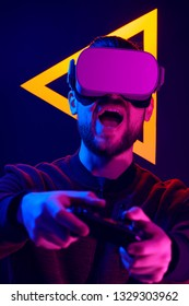 Man wearing virtual reality goggles playing video game with gamepad joy stick controller. VR head set videogame in 80's synth wave and retro wave glowing triangle futuristic aesthetics.