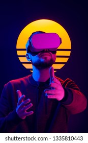 Man wearing virtual reality goggles and interacts video game with hand gestures. VR head set videogame in 80's synth wave and retro wave futuristic aesthetics.