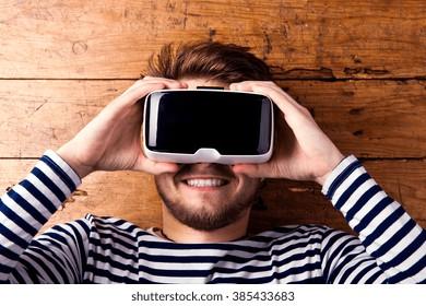 Man wearing virtual reality goggles. Studio shot, wooden background